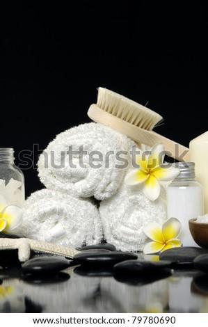 Spa still life with frangipani flowers, white towel and zen stone - stock photo