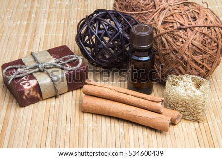 Spa still life with handmade natural soap ,aromatic oil, cinnamon and loofah on bamboo. Brown color