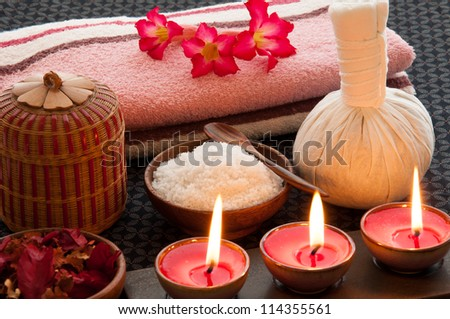 Spa still life with herbal massage ball, exfoliation salt scrub and spa accessories. - stock photo