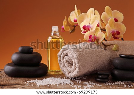 Spa still life with hot stones, essential oil and orchid - stock photo