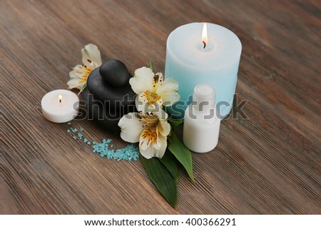 Spa still life with light blue candle on wooden background - stock photo