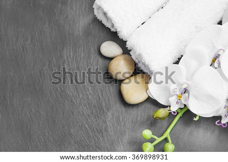 Spa still life with massage stones,white orchid and towels on grey background - stock photo