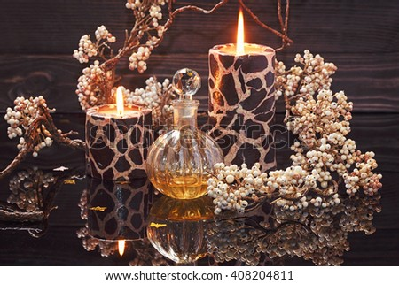 Spa still life with perfume and aromatic oils bottle surrounded by flowers and candles, on dark background - stock photo