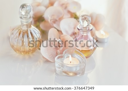 Spa still life with perfume and aromatic oils bottles surrounded by flowers and candles, on light background - stock photo