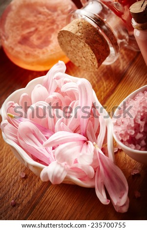 Spa still life with pink sea salt and flower petals on wooden background