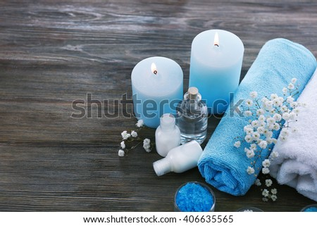 Spa still life with rolled towels and candlelight on wooden background - stock photo