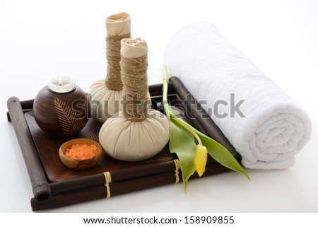 spa still life with spa herbal balls, candlestick, tulip, stones and salt in wooden bowl and white towel over white - stock photo