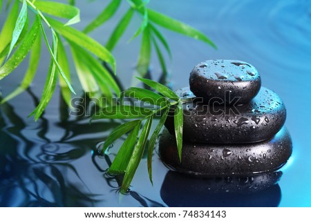 Spa still life with stone pyramid reflecting in water - stock photo