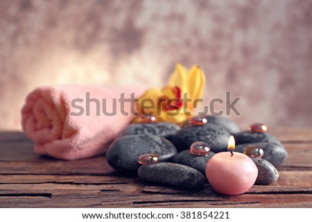 Spa still life with stones, towel, flower and candlelight on blurred pastel background - stock photo