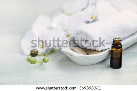 Spa still life with white orchid and towel, bath essence oil bottle - stock photo