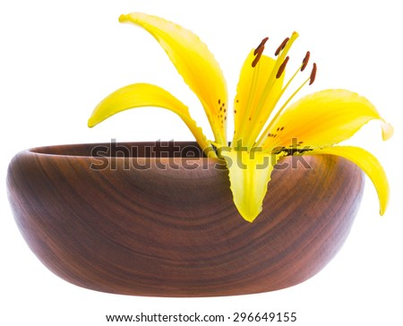 spa still life with yellow lilly in wood bowl  - macro lens shot - stock photo