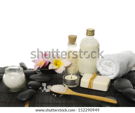 Spa still with salt ,oil in glass, frangipani, towel ,candle ,soap on black pebbles  - stock photo