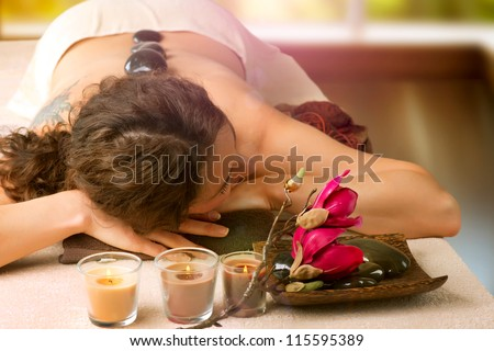 Spa Stone Massage. Day-Spa Treatment. Beautiful Woman in Spa Salon. - stock photo