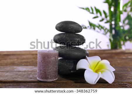 Spa stones, a candle and a lotus, isolated on white