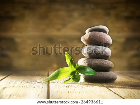 Spa stones and bamboo on wooden background - stock photo