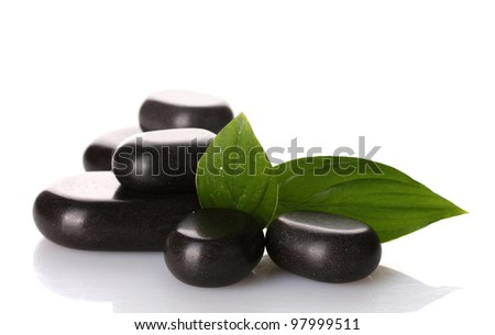 Spa stones and green leaves isolated on white