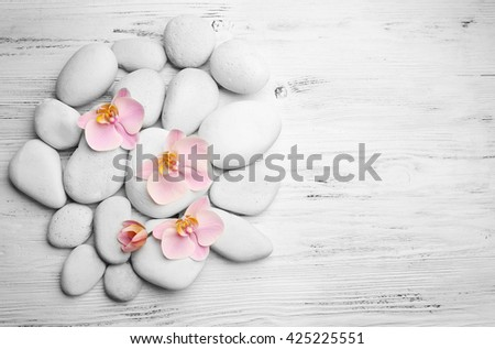 Spa stones and orchid flowers on wooden background - stock photo