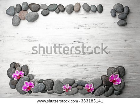 Spa stones and orchids on wooden background - stock photo