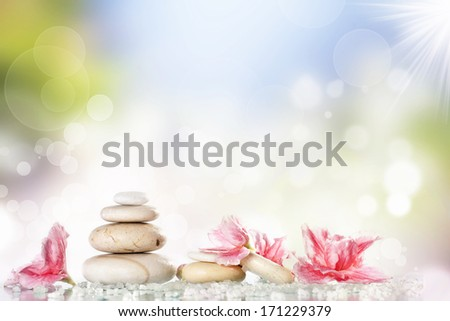 Spa stones and pink flower on colorful spring background  - stock photo
