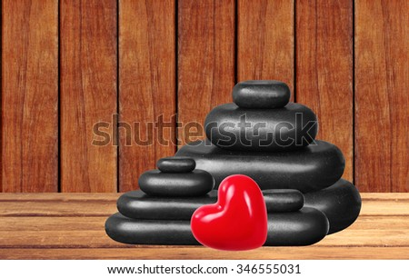 Spa stones and red heart on wooden table over wooden background - stock photo