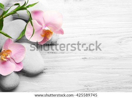 Spa stones, bamboo stack and orchid flowers on wooden background - stock photo