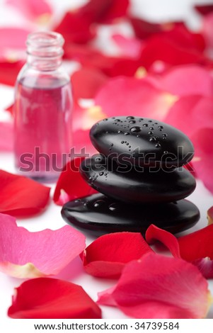 spa stones, essential oil and rose petals