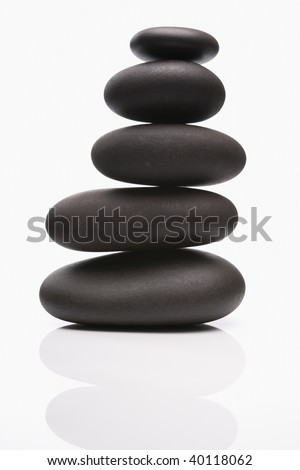 Spa stones in perfect balence on reflective white background - stock photo