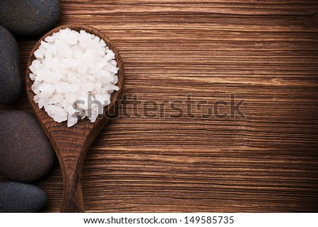 Spa stones in the wooden spoon, wood background. - stock photo