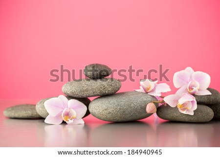 Spa stones on pink background with orchids. - stock photo