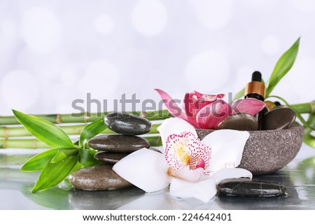 Spa stones, orchids, bamboo branches and aroma oil on table on light background