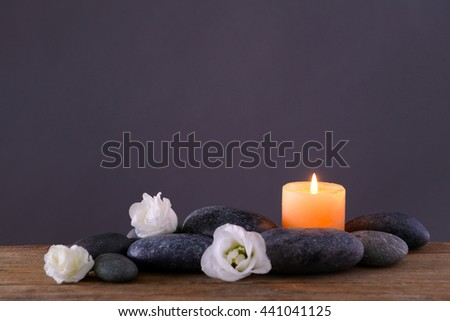 Spa stones with burning candle and flowers on grey background - stock photo
