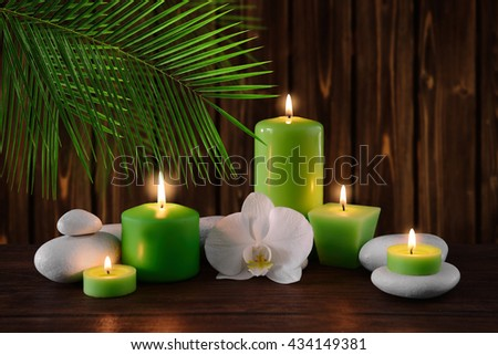 Spa stones with burning candles and flowers on wooden background - stock photo