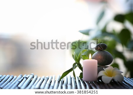 Spa stones with candle and tropical flower on blurred background - stock photo