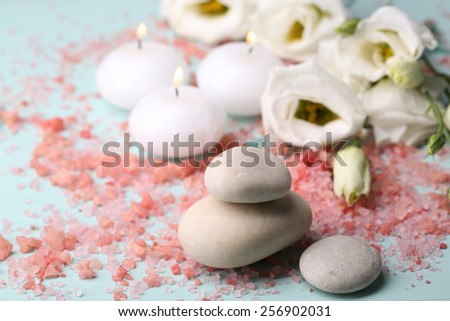 Spa stones with candles and flowers on blue background close-up - stock photo
