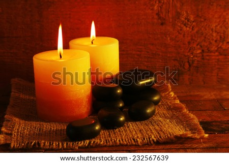 Spa stones with candles on wooden background - stock photo