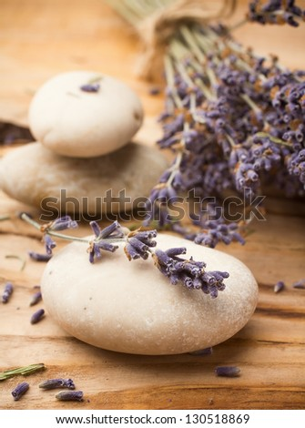 Spa stones with dried lavender flowers. - stock photo