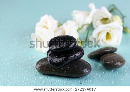 Spa stones with drops and flowers on blue background close-up - stock photo