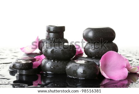 Spa stones with drops and rose petals on white background