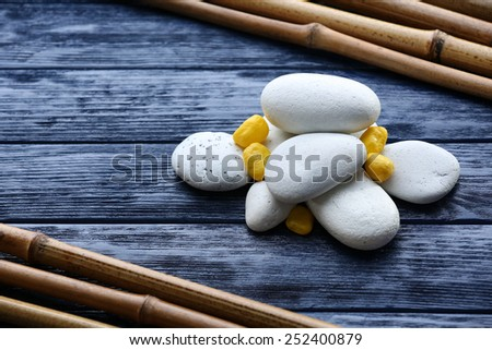 Spa stones with dry bamboo on wooden background - stock photo