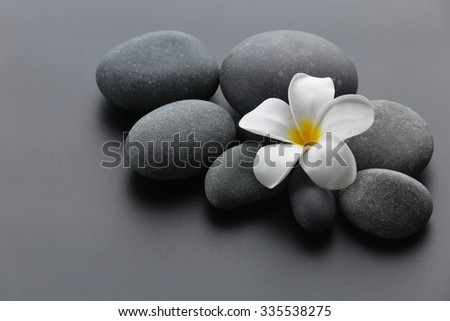 Spa stones with flower on gray background