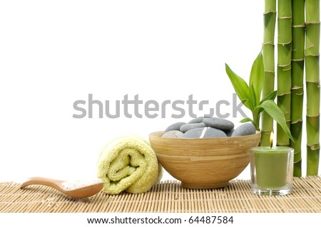 Spa style Towel with Bamboo, bowl of Massage Stones and candle - stock photo