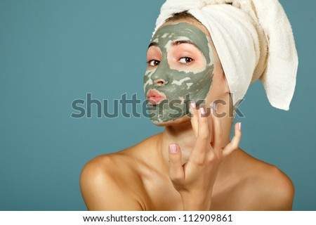 Spa teen girl applying facial clay mask. Beauty treatments. Over blue background. - stock photo