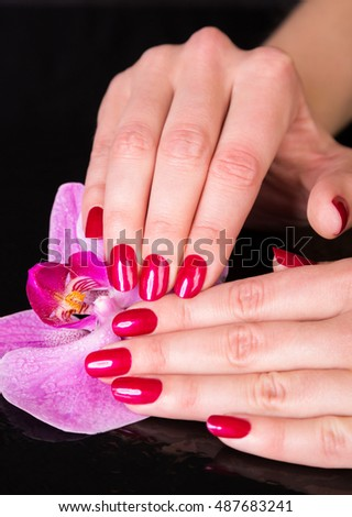 Spa theme close up over top of pretty hands next to purple iris flower over black background
