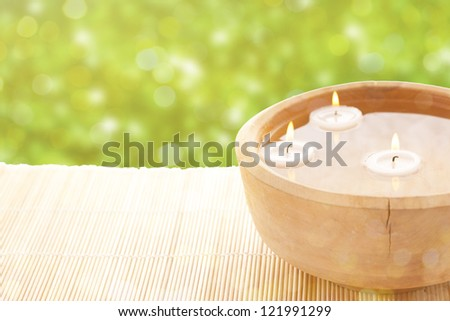 Spa therapy, flowers in water, on a bamboo mat. - stock photo