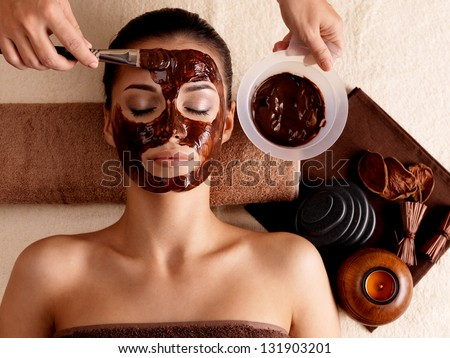 Spa therapy for young woman with cosmetic mask at beauty salon - indoors - stock photo