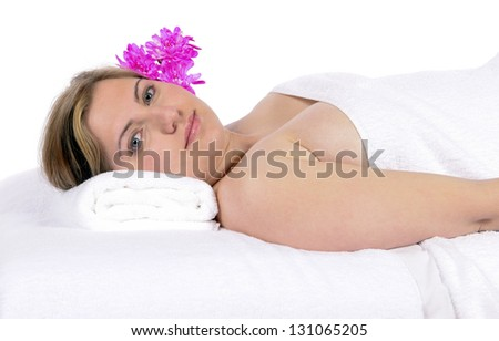 Spa therapy pretty young blond woman looking at camera, partial nude enjoying aroma therapy covered with towel laying on massage table. In studio on white background. - stock photo