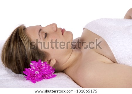 Spa therapy pretty young blond woman, partial nude enjoying aroma therapy covered with towel laying on massage table. In studio on white background. - stock photo