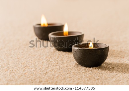 Spa therapy three candles on sand still nature - stock photo