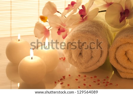Spa towels, candle and orchid on bamboo background - stock photo