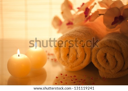 Spa towels, candle and orchid on bamboo background. Focus On Foreground. - stock photo